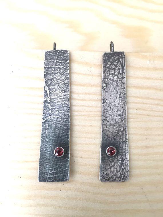 Estos pendientes de plata esterlina se inspiran en la libélula. La pátina de plata aplicada crea y antiguo, usado con el patrón sutil ala plateado mostrando a través de. Dos granates facetados rojos se sientan en la cima de cada creación una sensación orgánica animada.  Estos son uno de los tipos. Longitud total de pendientes son 1 3/4 pulgadas.