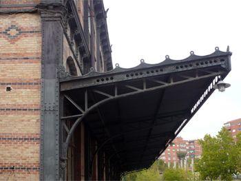 Marquesina de hierro del antiguo vestíbulo en el pabellón de salidas del edificio de viajeros. Muros de fábrica de ladrillo con franjas de dos tonalidades de rojo y decoración pintada en negro.