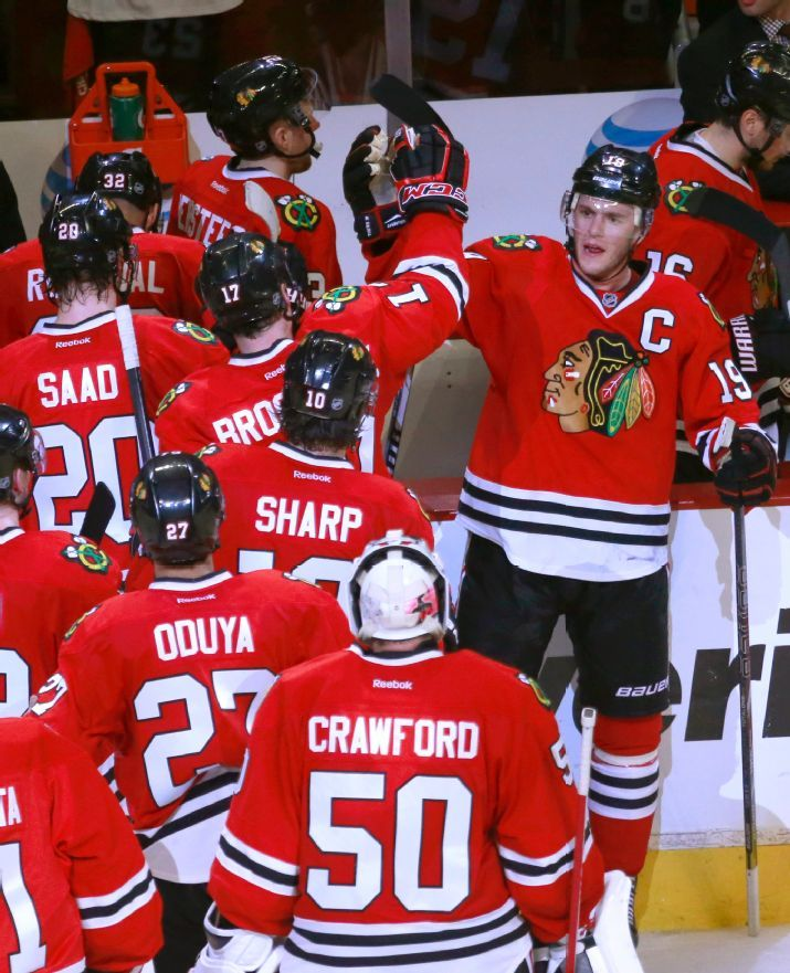 Chicago Blackhawks center and Captain Jonathan Toews, right, celebrates with his teammates after the Blackhawks' 2-0 win over the St. Louis Blues after Game 3 of a first-round NHL hockey Stanley Cup playoff series game Monday, April 21, 2014, in Chicago. (AP Photo/Charles Rex Arbogast)
