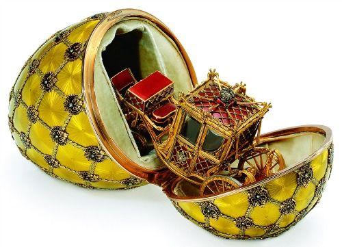 uovo dell'incoronazione -La sorpresa celata all'interno dell'uovo, in un vano rivestito di velluto, è un dettagliato modellino, lungo meno di dieci centimetri, della carrozza imperiale risalente al XVIII secolo utilizzata dalla zarina Aleksandra per le cerimonie dell'incoronazione nel 1896.  Il rosso della carrozza originale è stato riprodotto con smalto traslucido color fragola, usato anche per i sedili imbottiti dell'interno, dietro i quali la tappezzeria è in smalto azzurro.