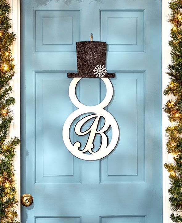 Add a touch of winter decor to your home with this Monogram Snowman Door Hanger. The laser-cut snowman silhouette features a scrolled initial inside the bottom circle and wears a top hat adorned with a glittery snowflake. Hang on the front door using the