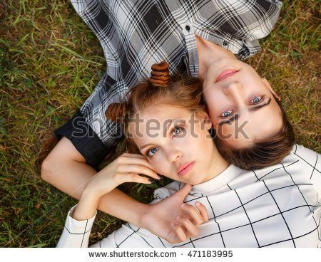 Sweethearts Teens lying on the grass head to head. Girlfriend and boyfriend together. First love. He falls in love. Date.