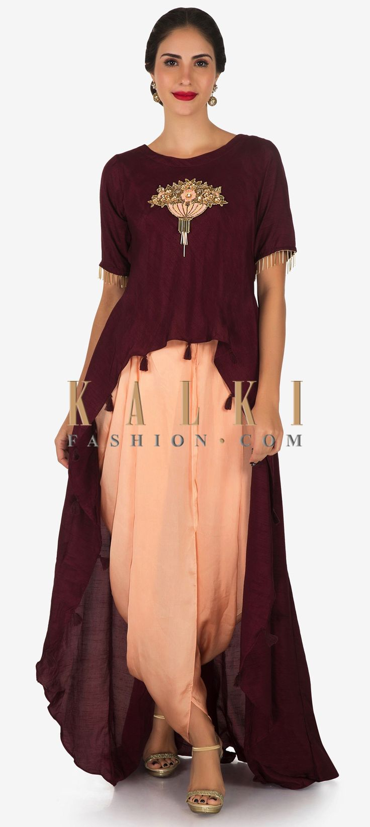 Buy Online from the link below. We ship worldwide (Free Shipping over US$100) Click Anywhere to Tag Maroon and peach dhoti suit with a over layer embellished in resham and sequin butti work only on Kalki Take your style game a notch higher in this maroon and peach dhoti suit. The dhoti suit is set together with a raw silk crop top that acts as a base for the outfit. Further it extends to a over layer with a front short and long back that is embellished in resham and zardosi butti at the…