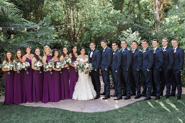 Los Angeles outdoor wedding at eden gardens bride mermaid style gown with crystal beading and off the shoulder straps with sweetheart neckline and groom navy blue tuxedo coat with black pants and black vest with white dress shirt and black bow tie with white floral boutonniere with bridesmaids long purple dresses and groomsmen navy blue suits with long black ties