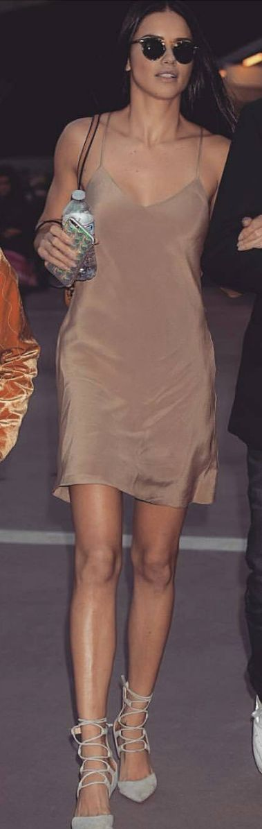 Who made Adriana Lima's tan slip dress, brown handbag, gray suede lace up boots, and sunglasses?