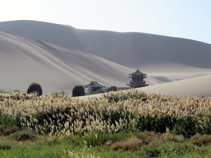 The Mingsha Sand Dunes almost engulf the Mingyue Pavilion at Crescent Lake just south of Dunhuang, Gansu, China.