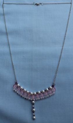 "This necklace has a row of pink transparent beads with white pearl and transparent beads. It also features purple seed beads on a silver plated chain. 58.5cm (23"").  Materials used: Glass, acrylic and a silver plated chain."
