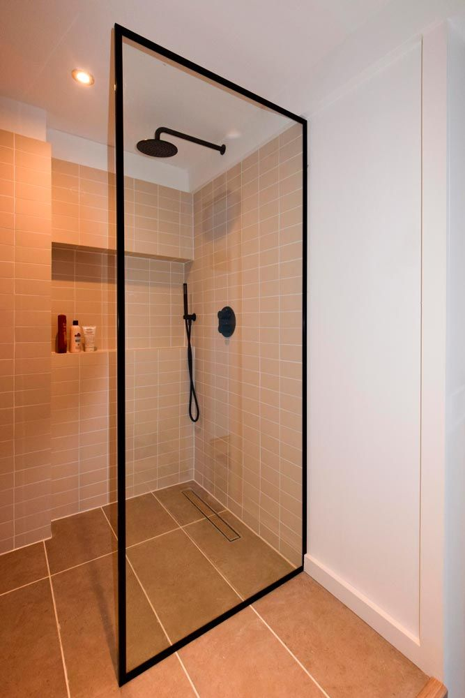 Black frame shower screen made by Creative Glass Studio in London. Easy clean 10mm toughened glass screen