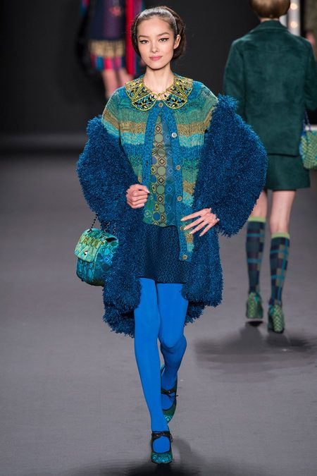 Anna Sui Fall 2013 RTW - Indigo, Turquoise Blue, Emerald Green, & Gold Mixed patterns.  Gold collared striped cardigan, fuzzy coat, & blue tights, with patterned blouse, skirt, purse & shoes