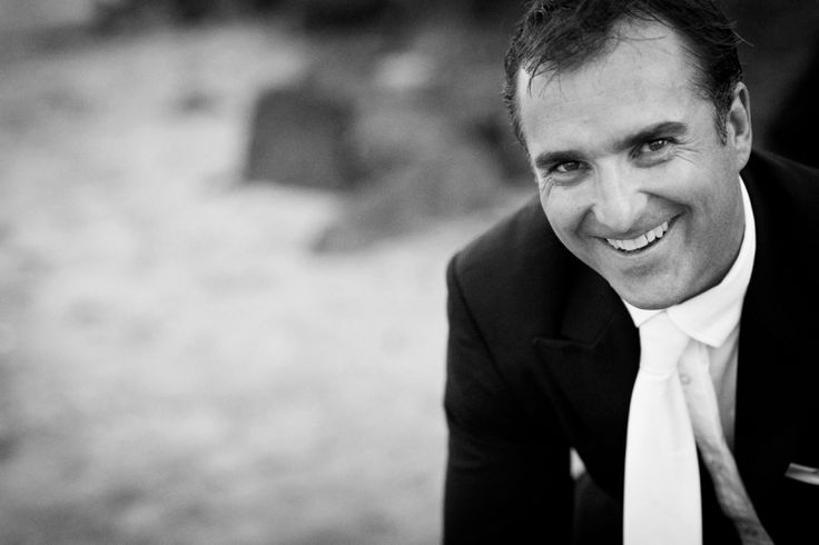 Groom smiling at the camera after his wedding at home at Milford beach, Auckland. Black and White.  beguiling fine art family photographs for the walls of the most discerning clients homes. We specialise in wedding and family portrait photography, and supply prints on the highest quality media, framed in beautiful conservation standard frames. We are a high end studio located in the beautiful city of Auckland, New Zealand.