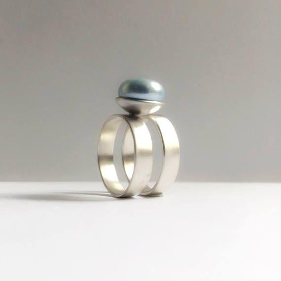 Deze dubbele ring draagt een 11 mm grote blauwe parel. De kleur van de parel is variabel en kan parelmoerkleurig wit, taupe en roze. de breedte van de beide ringen is 5 mm, in totaal is de ring ca 13 mm breed en in alle ringmaten verkrijgbaar. De ring heeft een matte afwerking.