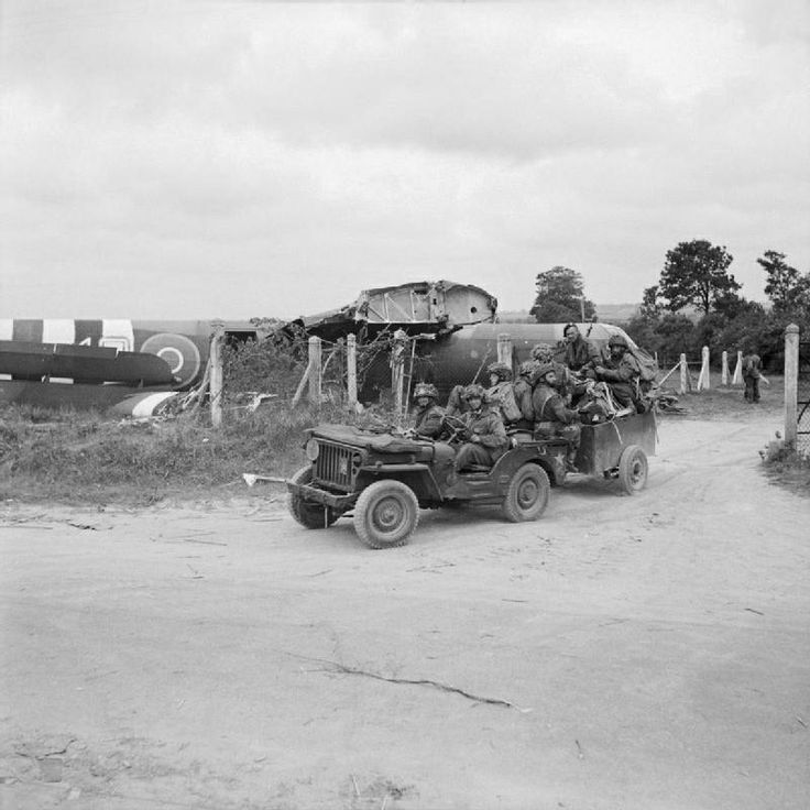 """Paras of 1st Battalion, Royal Ulster Rifles, 6th Airlanding Brigade, 6th Airborne Division, aboard a Jeep and trailer, past a crashed Airspeed """"Horsa"""" glider, Landing Zone 'N', north of Ranville, Normandy, France. 6 June 1944."""