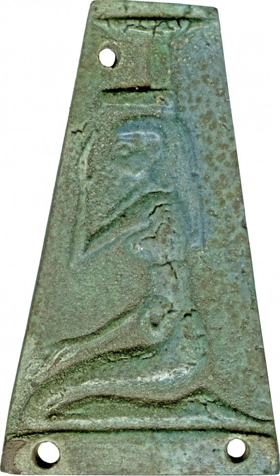 """Amuletic Plaque with Nephthys ca. 400-250 BC (Late Period-early Greco-Roman)  Egyptian faience with pale green and blue glaze The goddess kneels upon a low base and holds her right hand in front of her face in a gesture of mourning. She wears a long sheath gown and a tripartite wig. Her characteristic headdress is actually a hieroglyphic writing of her name: a """"nb"""" basket on top of a """"hwt"""" shrine/mansion. Her name means """"Lady of the Mansion."""""""