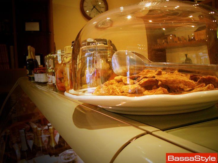 """Un vassoio dei tipici """"ciccioli"""" per stuzzicare l'appetito, insieme alle salse e ai sughi pronti di ottima qualità in fila sul banco"""