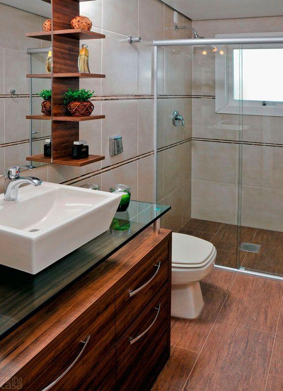 Com um estilo mais rústico, este banheiro recebeu piso de porcelanato que imita madeira de demolição. Faixinhas de pedra contornam as paredes e se harmonizam com o porcelanato bege. A marcenaria de MDF recebeu acabamento de laminado melamínico no padrão madeira. Projeto de Letícia Laurino Almeida.