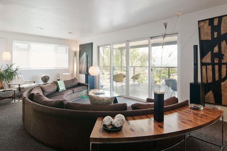 un canapé demi lune marron et surdimensionné, une table console de design ovale et une table basse en verre