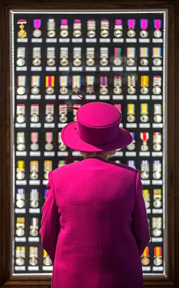 Queen Elizabeth II looks upon a cabinet of medals during a visit to the medal…