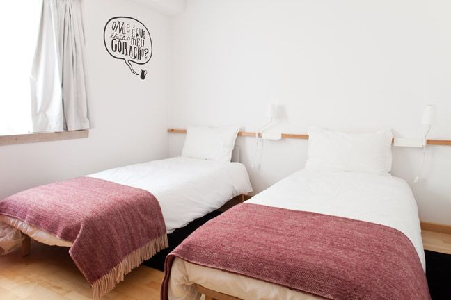 The Lisbonaire Apartments, available for holiday rental in Lisbon. Detail of bedroom, wall design by João Maio Pinto. Handmade blankets by Saberes e Fazeres da Vila.