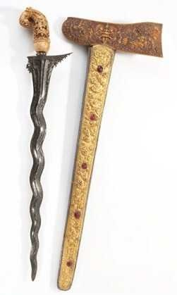 The Kris or Keris is a dagger that originates from Indonesia and Malaysia. Kris knives with decorative scabbards are used throughout Indonesia as weapons and ritual objects, and are part of men's ceremonial attire. The wavy iron blade of the knife represents a snake in movement and is thought to have power to protect its owner. In the past disputes were settled with this double edged dagger. The more people it killed the more valuable it became.