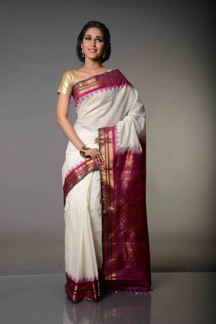 Kusuma Parag White and Purple Gadwal Silk Cotton Saree : White and Purple combination with a tinge of green, Kusuma Parag White and Purple Gadwal Silk Cotton Saree is a descendent of Gadwal Sico Sarees. With the pallu themed around flowers, it gives an impression that delicate small flowers dipped in gold, have been beautifully arranged in a line.