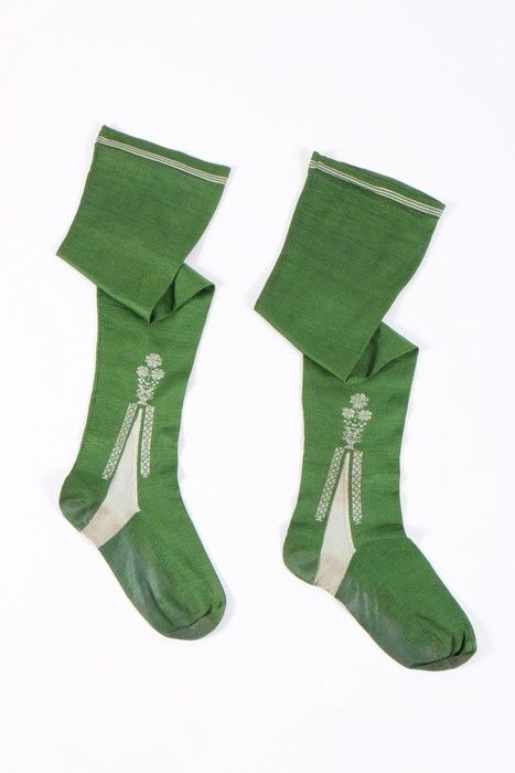 Pair of woman's stockings, England or France, 1750-1770. Frame-knitted green silk, the ivory clocks edged with diapered bands and pots of blooms, stripped upper edge.