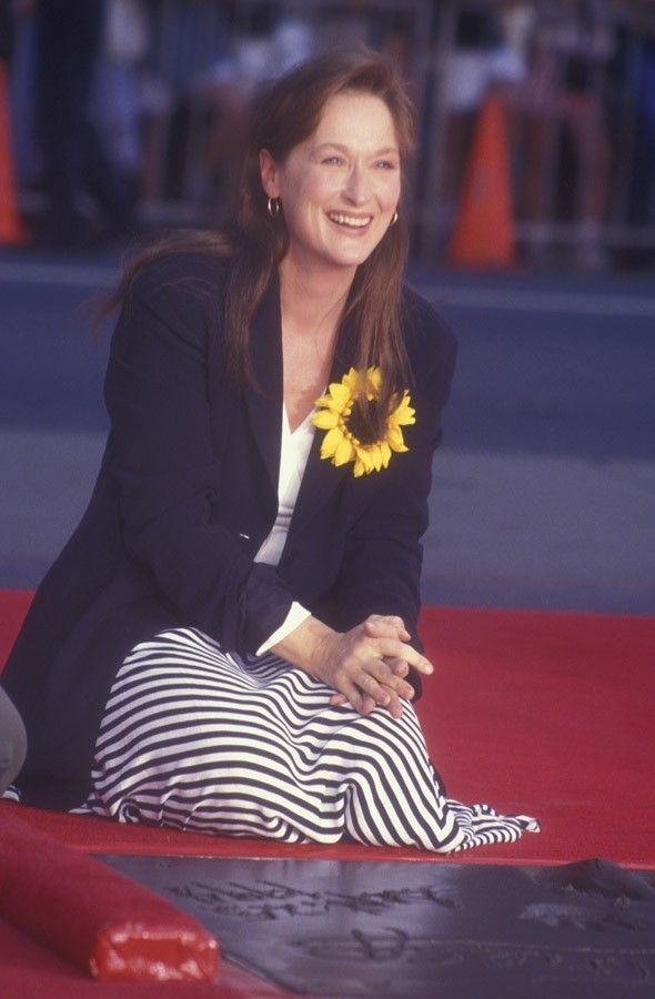 Style Evolution: Meryl Streep - via MyDaily  Footprint Ceremony, 1994 When the actress stamped her mark on the Hollywood walk of fame, her trademark blonde hair was gone in favour of a darker 'do. She kept her fashion simple for the occasion using a sunflower to add a whimsical touch for the celebratory occasion. (Source: Getty)