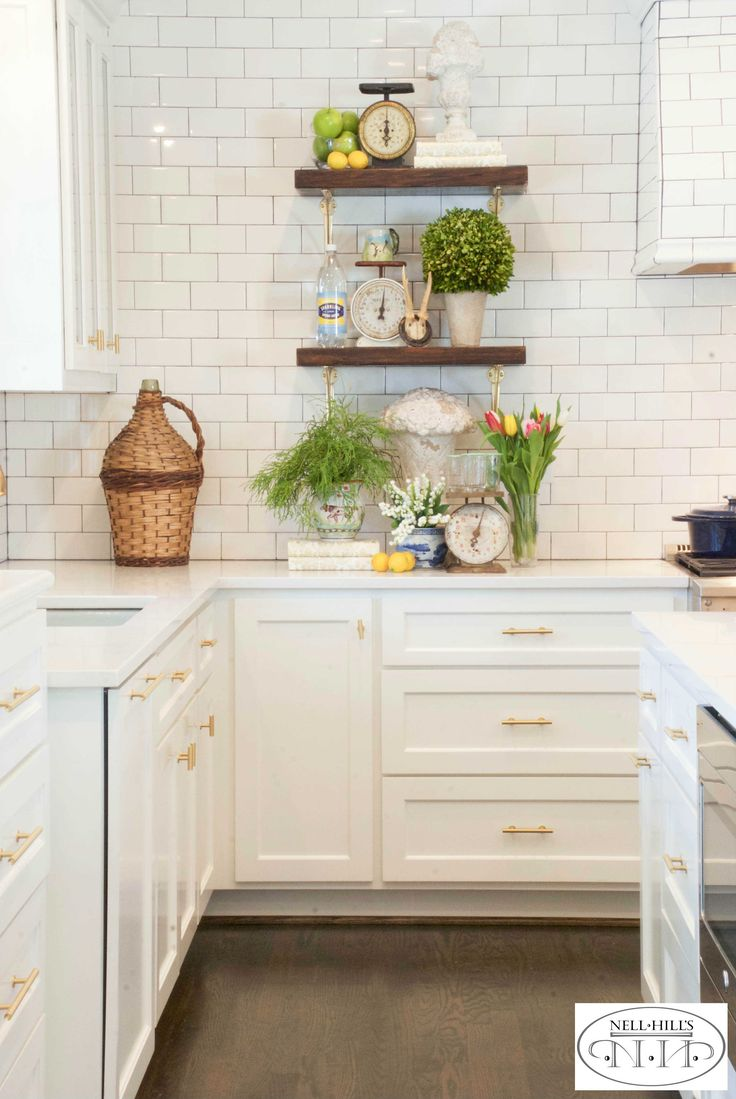 The white tiled walls in this kitchen are jazzed up with shelves made of reclaimed wood, filled with seasonal accents.