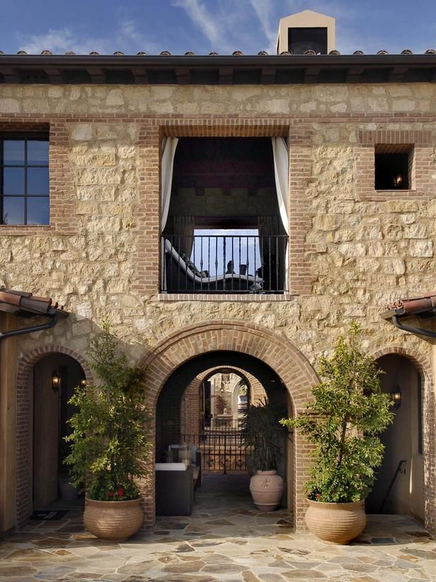 Home Exterior Hardscaping: The hardscaping perfectly complements the texture and neutral color palette of this Mediterranean home. From HGTVRemodels.com