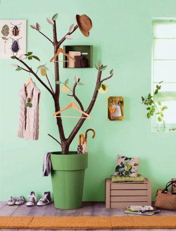 Portemanteau en forme d'arbre avec branches plantées dans un pot et feuilles en papier