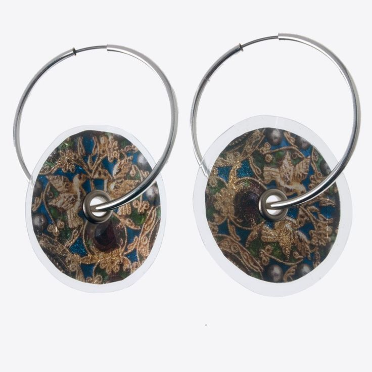 Digitally printed earrings with traditional Greek embroidery motifs. Made of silver leaf and plastic film. Stamatis Zannos designs jewels inspired by the contemporary Greek civilization as it is showcased in museums. Zannos has presented his work in several venues, including the Benaki Museum in Athens.