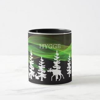 """Nordlyskruset,Krus for kaffe eller te i nordisk stil, høyde 9,5 cm diameter 8 cm. Illustrasjoner inspirert av norsk skog. Med hvite silhuetter av granskog, elg, rev og hare. Med grønne og gule """"bølger"""" som skal illustrere nordlys. Svart bakgrunnsfarge. Med teksten: Hygge Kruset har svart håndtak, og har svart glassur på innsiden."""