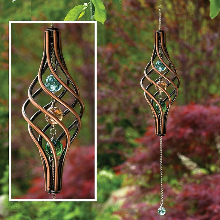"Watch this kinetic copper-finished wind sculpture as it gracefully spins in the wind. The twisted cage holds 3 iridescent marbles with 1 additional marble that swings from the metal chain for a stunning visual effect. 22"" long, ready to hang."