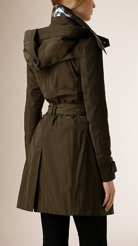Burberry Dark Olive Hooded Showerproof Trench Coat -  A lightweight trench coat crafted from technical showerproof fabric with a detachable hood. The double-breasted trench coat is cut for a relaxed fit with a structured shape engineered by set-in sleeves and a belted waist.  Discover the women's outerwear collection at Burberry.com