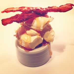 A Crepe with dollops of mascarpone cheese topped with crispy bacon and drenched in golden syrup