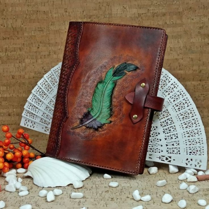 "Feather Notebook cover (No Shipping Costs - In stock) A beautiful handcrafted leather notebook cover decorated on the front with a hand carved, hand painted feather. It holds an A5 size notebook with a simple strap to close. The spine is decorated with a tooled basket weave. The inside is lined with soft pig skin for an elegant look and feel that you will only find in hand crafted items. (Approx. size closed: height - 22.5cm (9""); length - 16.5cm (6.5""), width - 2cm (0.79"") #b2zoneservice"
