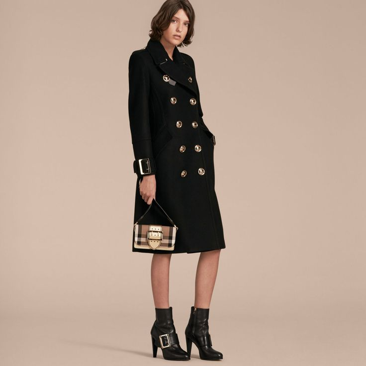 A military coat in a sumptuous wool-cashmere blend with domed buttons and distinctive buckled throat latch and cuffs. Tailored with feminine proportions, the silhouette has a cinched waist and full skirt accentuated by inverted pleats and a martingale at the back.