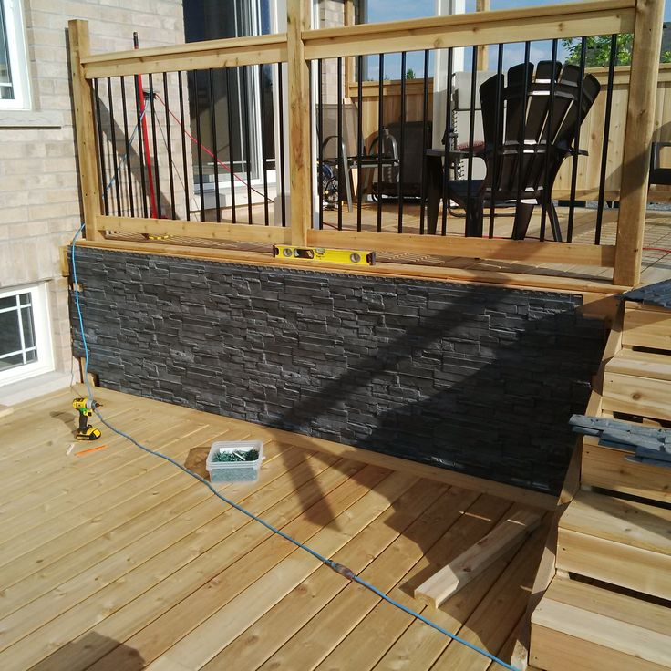 coated aluminum balusters go nicely with the black faux stonework.