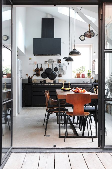 I love the simple pot hanging hooks in this industrial/contemporary kitchen. They're right where you need them within easy reach above the stove and the pots themselves add to the deconstructed flair of this kitchen. This display idea works particularly well if you have a cohesive pot collection — think all black or copper. I love the simple matte black hood and streamlined cabinets here as well.
