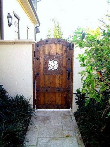 Heavy wooden gates with wrought iron very spanish for Exterior garden doors