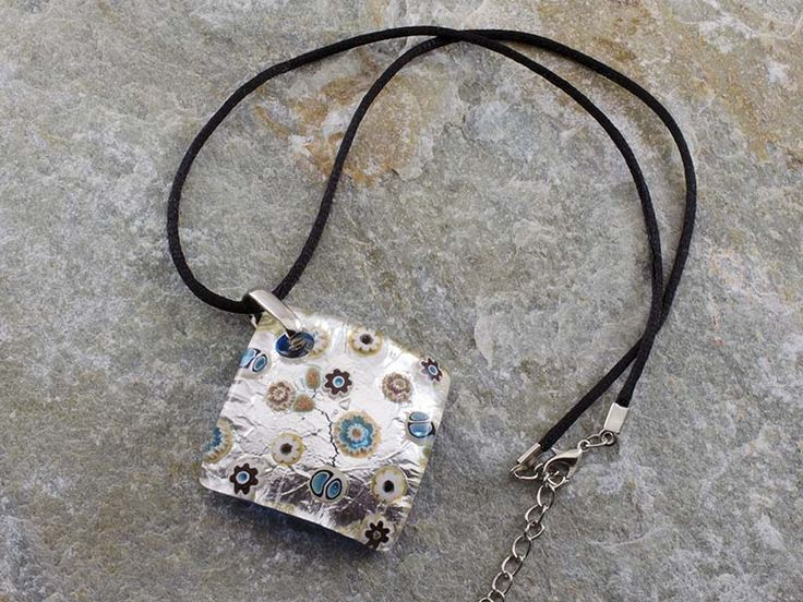 Collana pendente in vetro di Murano con piastra a rombo e bombata con foglia di argento e murrine Il cordino è in alcantara di colore nero