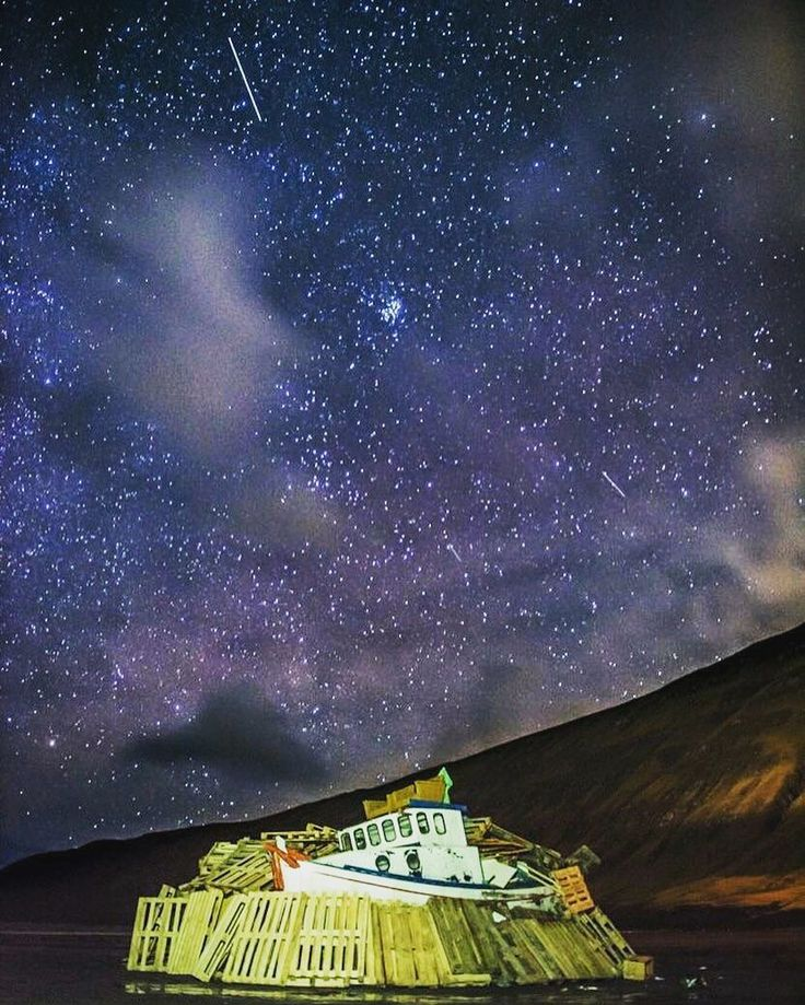 Our @jameskelly_photo is finally getting round to editing photographs from his visit to the Faroe Islands in December/January. A break in the storm on New Year's Eve allowed him to capture this shot of the bonfire on Sandvík beach.  #FaroeIslands #newyear #stars #boat #startrails #longexposure #nightlife #igersaberdeen #stars
