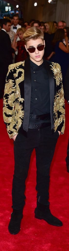 Justin Bieber let his dragon-covered Balmain design take center stage by opting for an all-black foundation of simple pants, suede booties, a collarless button-up, and a thick satin belt.