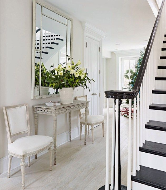Weekend whites! A pair of Swedish Gustavian chairs and console table from our shop in this beautiful home designed by our good friend Frank Babb Randolph. Love the high gloss black with the bleached floors! Photo from Traditional Home magazine. #toneontoneantiques #gustavian by loithai