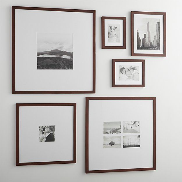 classic brown wood and extra wide white mat frames in a modern gallery