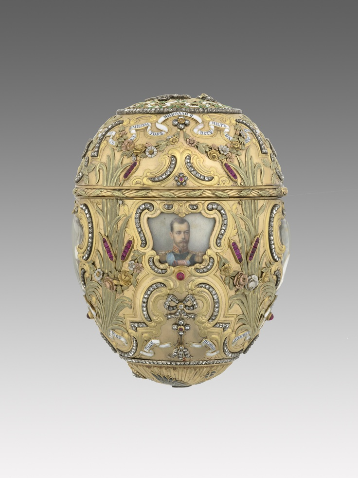 """""""The Emperor Nicholas II gave this Egg to his wife, the Empress Alexandra Fedorovna for Easter 1903. It commemorates the 200th anniversary of the founding of Saint Petersburg by Peter the Great. Its body of varicoloured gold is in the rococo-revival style and was inspired by a French nécessaire with a clock that is still in the Hermitage. The body of the Egg is rich in symbolism. In Russia roses and laurel leaves represent triumph and pride. The bulrushes shown in our image to the left and…"""
