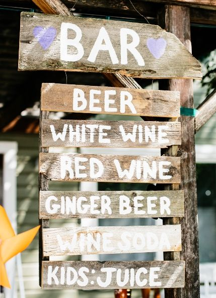 Hand-written wooden bar sign at wedding reception.