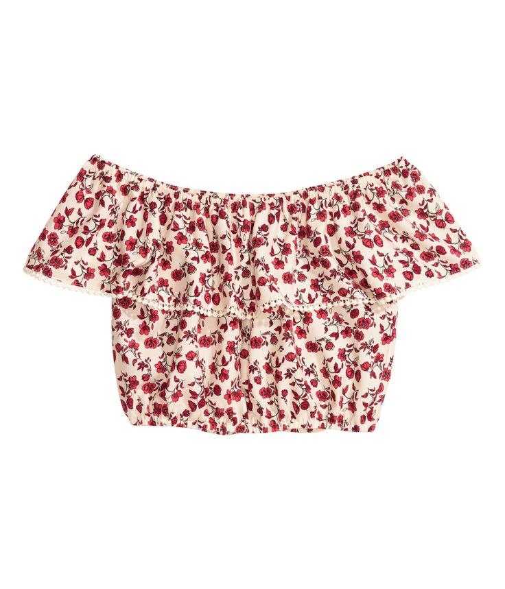 Hvit/Rød blomstret. En kort off-shoulder bluse i vevd kvalitet med trykt mønster. Blusen har elastikk og bred volang øverst. Korte ermer. Elastikk nederst.
