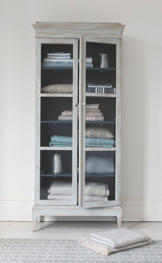 Our Flummery glass fronted cabinet with an inky blue interior and scuffed white exterior. Perfect for stacking clean laundry in the bathroom or ingredients in the kitchen