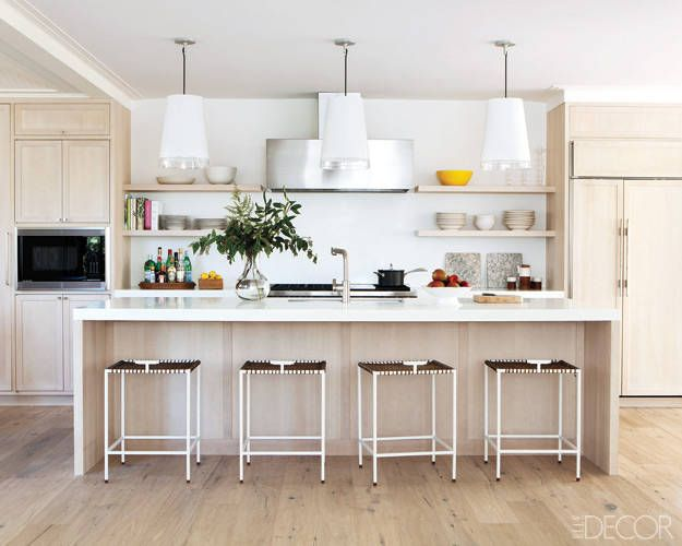 The kitchen's pendant lights are from Resolute, the Corian-top island and ash-veneer cabinets are custom made, and the stools are by Samare.