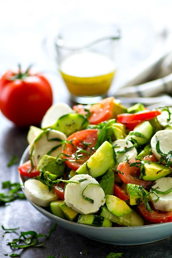 This Italian-style tomato avocado salad is loaded with tons of fresh tomatoes, avocados, cucumbers, and soft mozzarella cheese for one killer summer salad! - Emily Horvath